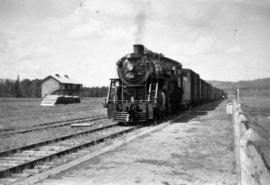 Steam locomotive, track and a building in an unknown location