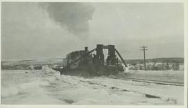 Four unidentified men standing on a railroad snow plow connected to the front of a train which is...