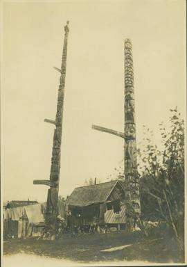Man standing between two totem poles