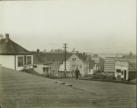 Unidentified man walking up a wood planked street in Prince Rupert, BC