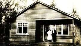 Mr. and Mrs. Collins standing on the porch of their house