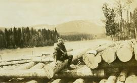 Man sitting on top of a large log pile