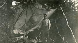 "A. H. Holland in camp with dog ""Stubs"""