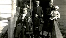 Marion and W.H. Collison posing with grandchildren on porch at Kincolith, BC