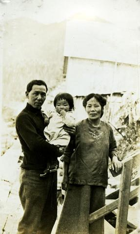 Photograph depicts an asian (likely Japanese or Chinese) couple with a baby, possibly at Nass Harbour.
