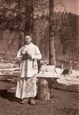 [Military chaplain reading by a makeshift tree stump altar]