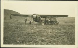 Men Standing by Airplane in Field
