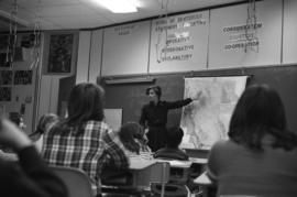 Iona Campagnolo pointing at a map of BC and talking to Haida Gwaii students