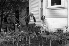 Iona Campagnolo talks with unidentified man in home garden