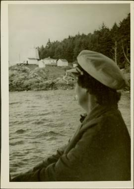 Woman seated in a boat looking at a lighthouse