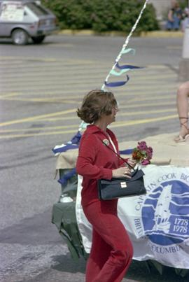Iona Campagnolo holding flowers while jogging in the Kitimat Captain Cook Bicentenary parade