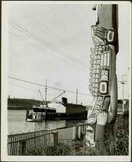 Close-up of Totem pole overlooking a wharf and the Camosun vessel