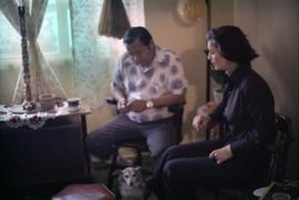 Iona Campagnolo and First Nations man sitting in living room with small dog