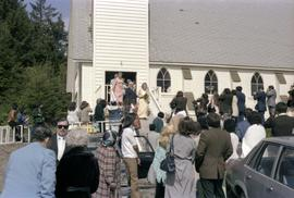 Godfrey and Vicki Kelly on church steps with crowd at 50th wedding anniversary celebration in Masset