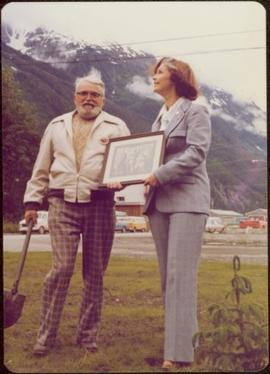Iona Campagnolo presents framed archival photograph to Waidlow Stewart at the Stewart Museum