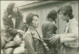 Unidentified man and woman talking to Iona Campagnolo in front of a Tsimshian longhouse
