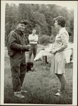 Iona  Campagnolo talking to an unidentified man outside while another man and a dog look on