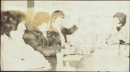 Two unidentified men and Iona Campagnolo sit around a table listening to an unidentified woman