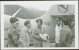 Unidentified woman, three unidentified men, and Iona Campagnolo stand talking in front of a small...