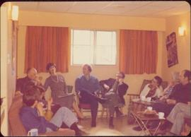M.P. Iona Campagnolo talking to nine unidentified individuals seated inside a curtained room, ca....