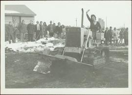 M.P. Iona Campagnolo waves from tractor in front of unidentified crowd