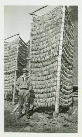 Mr. Huston stands in front of two tall racks of drying eulachon