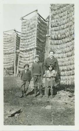 Mrs. Huston stands with three First Nations children in front of three tall racks of drying eulachon