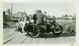 Five people ride a motorcycle and sidecar along the Port Simpson boardwalk
