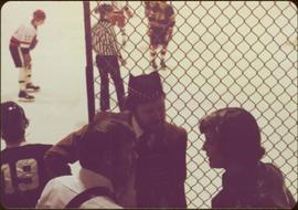 Two unidentified men speaking to Iona Campagnolo while a hockey game is played in background