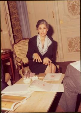 Paris Press Conference - Iona Campagnolo gestures while talking from chair at coffee table covere...