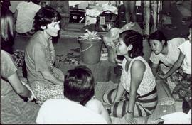 CUSO Mission, North-eastern Thailand - Unidentified woman kneels on floor with young girls