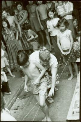 CUSO Mission, North-eastern Thailand - Unidentified boy walks between strings attached to a young...