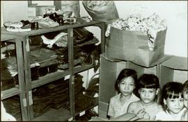 CUSO Mission, North-eastern Thailand - Unidentified children sit in front of shelves of clothing