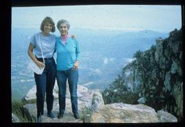 Iona Campagnolo and unidentified woman pose on a cliff above an unknown community overseas