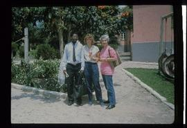 Iona Campagnolo standing outside with unidentified woman and man in front of a school at overseas...