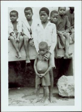 CUSO Mission in Waku-Kungo, Angola - Seven unidentified male children sit on a wall and stand in ...