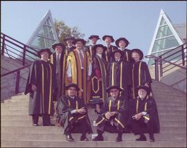Iona Campagnolo in group wearing regalia, posed on steps in the Agora Courtyard at UNBC