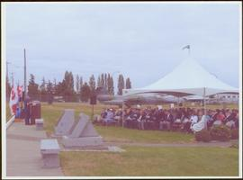 Air force officer speaking from a podium at the Comox Valley Air Force Museum
