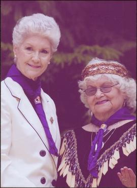 Lieutenant Governor Iona Campagnolo and an unidentified woman, both wearing purple scarves readin...