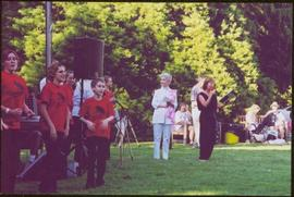 Lieutenant Governor Iona Campagnolo smiling at an outdoor function as youth in red t-shirts sing