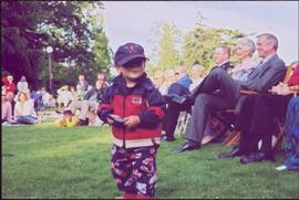 Lieutenant Governor Iona Campagnolo and crowd smile from lawn chairs, unidentified child in foreg...