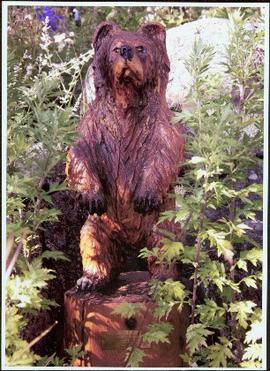 Chainsaw carving of a bear set among flowers in Terrace Gardens at Government House, Victoria, B.C.