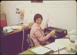 Alice Massad typing at her desk in the Ottawa office