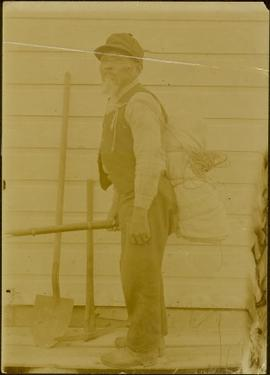 Arthur Wellington Clah carrying bundle and gun