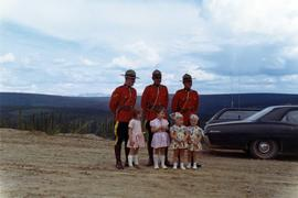 Three RCMP constables in dress uniform standing with four small girls in dresses