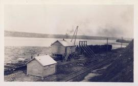 A sawmill with several logs in the water
