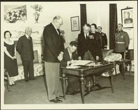 Ray Williston signing the register after being sworn in as a cabinet minister