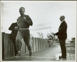 Ray Williston running through ribbon