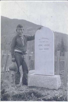 First Nations man standing to the side of a gravestone