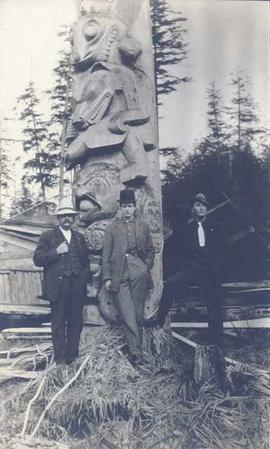 Three men standing in front of a totem pole